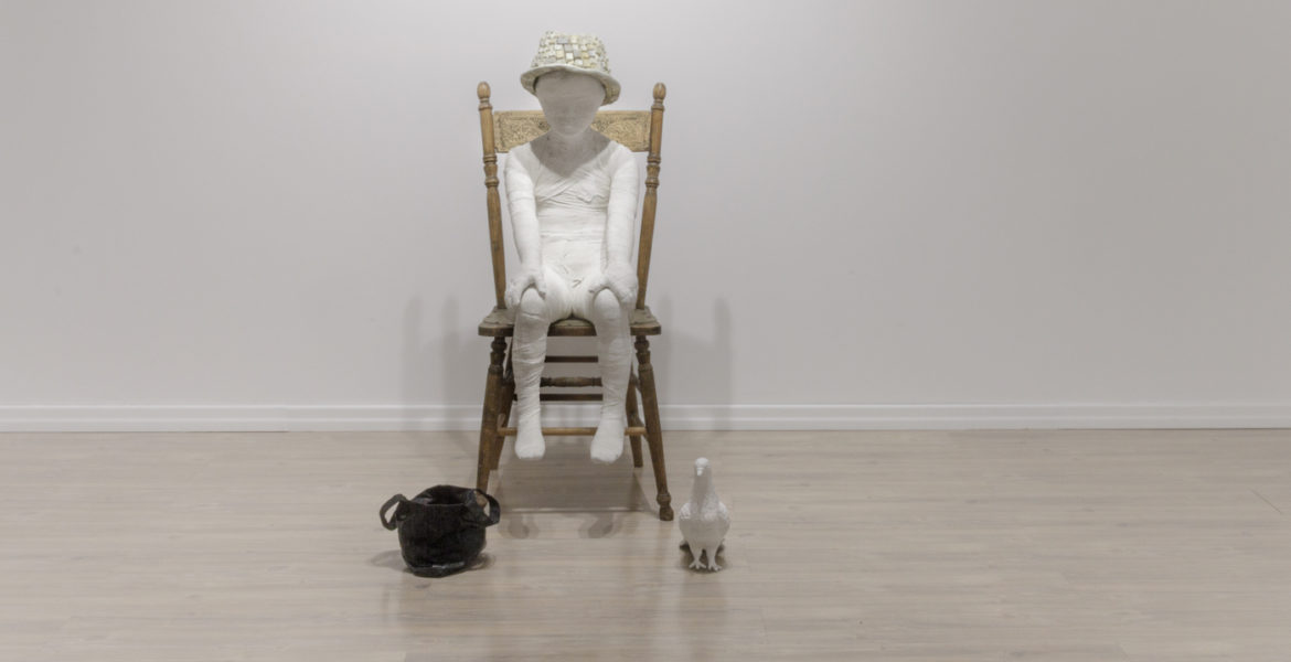 Sculptures of a boy sitting on a chair, dove and bag